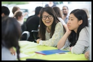International Students sitting at a table laughing